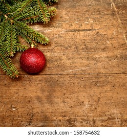 Red Christmas ball suspended on a green spruce twig old wooden background.