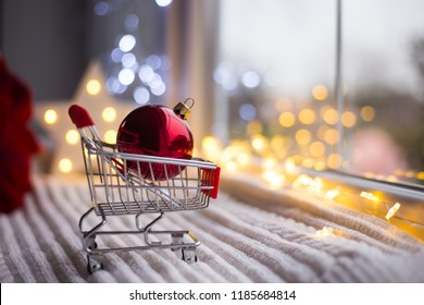 Red Christmas ball in toy supermarket trolley in daylight with warm garland bokeh on background. Festive magic lights. New Year shopping concept.