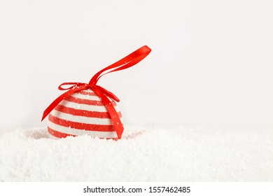 Red christmas ball with white dots and red ribbon in heap of fake snow on white background