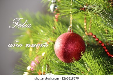 red christmas ball and the words happy new year in spanish, feliz año nuevo. red christmas ball on the tree.