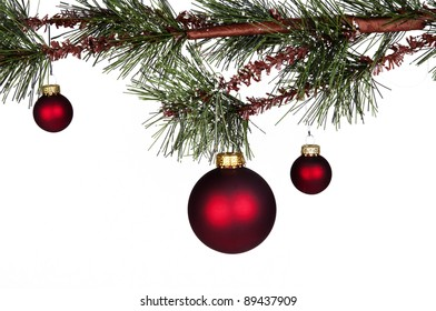 red Christmas balls hanging from a pinetree