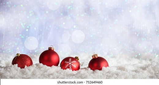 Red Christmas balls on abstract cold winter background with snow