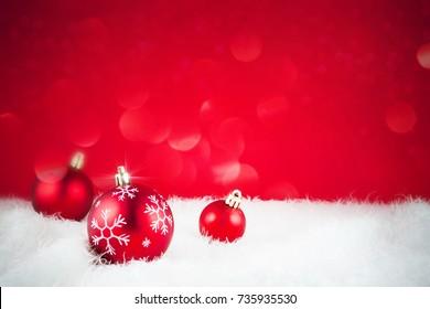Red Christmas balls on snow. Christmas decoration.