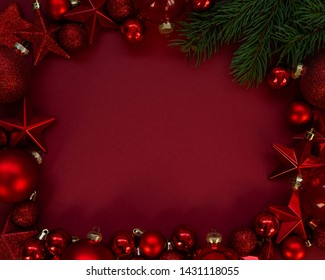 Red Christmas balls and stars decoration on red background with copy space. New Year greeting card. Top view with copy space for text.