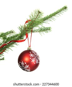 Red Christmas bauble hanging on natural conifer branch, isolated on white