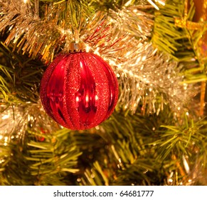 Red Christmas bauble hanging in a tree