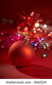 red christmas bauble over red background with assorted colours blurs