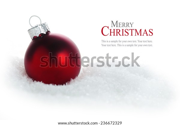 red christmas bauble in snow isolated on white background, sample text in the copy space, close up