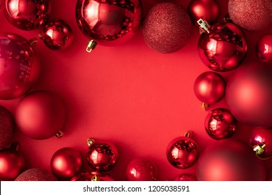 Red Christmas baubles decoration on red background with copy space. New Year greeting card. Minimal style.  Flat lay.