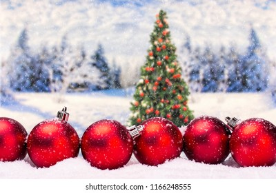 Red Christmas baubles as Christmas decoration with Christmas tree and landscape in the background