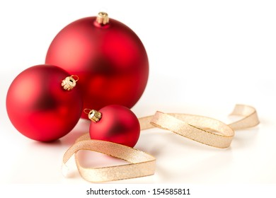 Red christmas baubles and gold ribbons on a white background