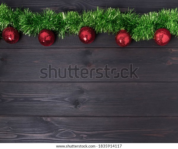Red christmas baubles and green tinsel on a dark wooden background, with room for copy space