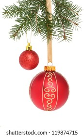 Red Christmas baubles hanging from a fir tree branch against a white background