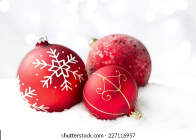 Red Christmas baubles on a white background