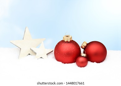 red christmas baubles and wooden star lying in snow