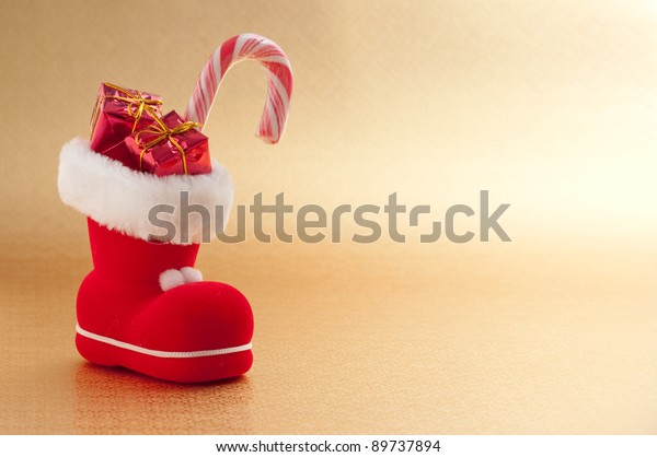 red christmas boot with gifts on gold background
