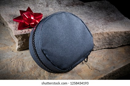Red Christmas bow and zippered tactical bag on beige stones