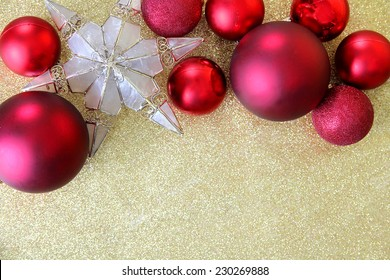 Red Christmas bulb decorations and a star shaped tree topper border the top of a background gold glitter fabric with copy-space.
