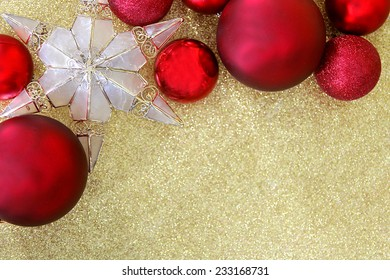 red christmas bulb decorations and a star shaped tree topper border the edge of a background