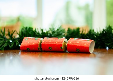 Red christmas cracker, on a table with green garland behind and fairy lghts