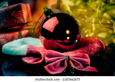 Red Christmas decoration ball for the Christmas tree surrounded by presents tinsels and Christmas decoration