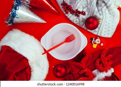 Red Christmas decoration on red background with white plastic plate and red fork. Concept of charitable aid to the poor and homeless on the New Year.