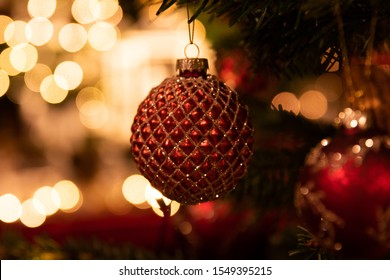 red christmas decoration on a christmastree with lights in the background