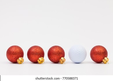 Red Christmas decoration and white golf ball on the white background