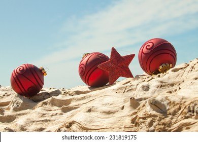 red Christmas decorations with sand and driftwood at a New Zealand beach