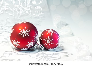 Red Christmas decorations with silver ornament on neutral winter background, text space. Shallow DOF, focus on two crowns