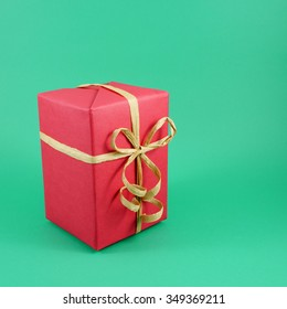 The red Christmas gift box with brown paper ribbon bow.