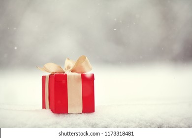 red Christmas gift box in the winter snow outdoors