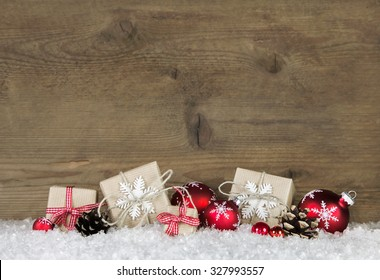 Red Christmas gifts wrapped in natural paper on old wooden grey background.