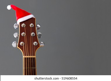 Red Christmas hat on guitar with grey background, Merry Christmas song