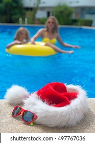Red christmas hat and sunglasses near the pool.