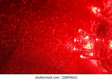 red christmas lights on twinkled paper background