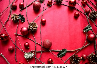 Red Christmas ornament balls with holly leaves on red background