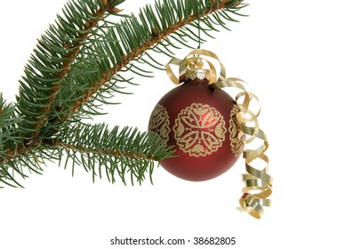 Red Christmas ornament with gold ribbon hanging from a pine branch isolated on white