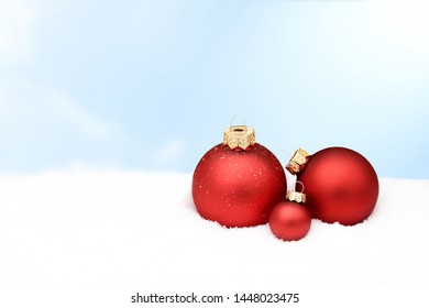 red christmas ornament lying in snow