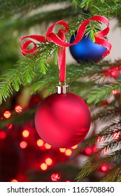 Red Christmas ornament tied with ribbon hanging from festive evergreen