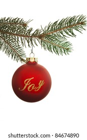 A red Christmas ornament with the word joy written on it.  It is hanging on a pine branch and set against a white background.