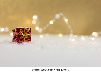 red christmas present in front of golden background