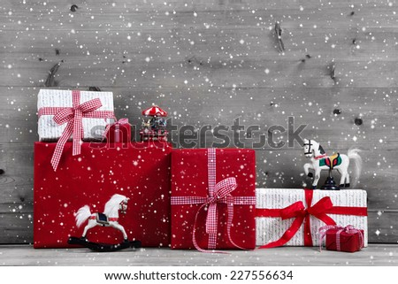 Red Christmas presents and gift boxes with rocking horse on grey wooden background.
