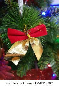 red christmas ribbon with gold ribbon on green branch