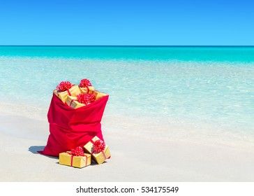 Red Christmas sack full of and surrounded by wrapped gift boxes at tropical ocean beach. Travel agency price reduction for Happy New Year hot tours destinations concept.