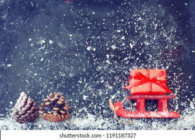 red Christmas sleigh carrying gift box, pine cones on black surface, snow, vintage style new year night composition