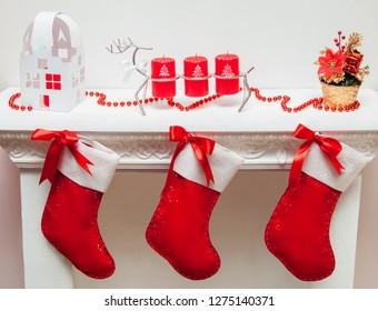 Red Christmas sock hanging on white fireplace