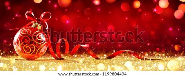 Red Christmas Sphere With Bow On Golden Glitter