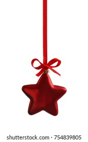 Red christmas star hanging on ribbon with bow, isolated on white.