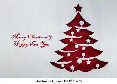 Red christmas tree cutout from white wooden board with rough texture covered by white paint - large copy space for seasonal greetings